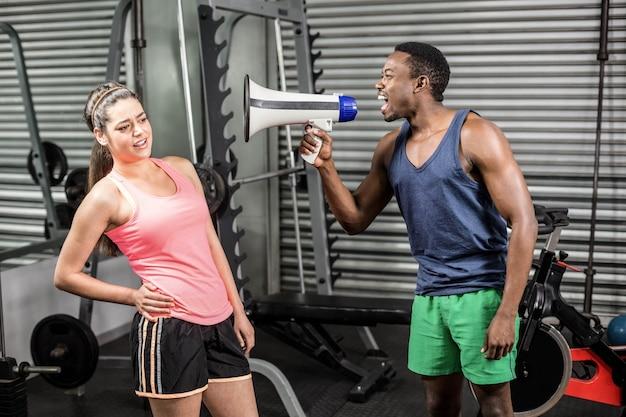 Formateur crier à la femme via un mégaphone à la gym
