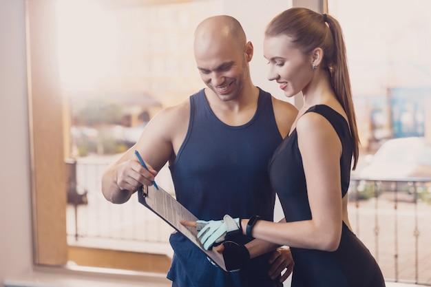 Formateur écrit un programme de fitness pour entraîner la fille