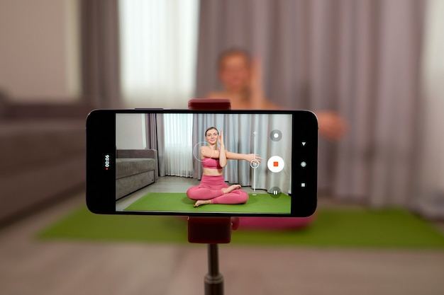 Le formateur enregistre les leçons de yoga. le formateur en direct montre comment faire des exercices correctement