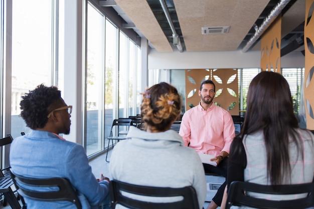 Formateur en entreprise partageant son expérience avec un groupe de collègues