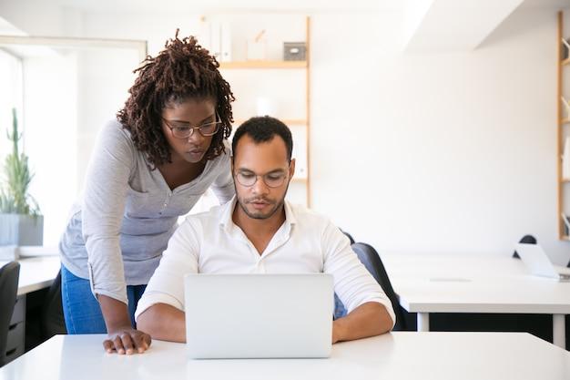 Formateur en entreprise regardant un rapport de rédaction