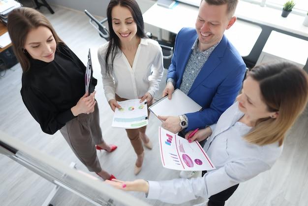 Formateur d'entreprise tenant des documents avec des graphiques dans ses mains et montrant des informations sur le public à bord