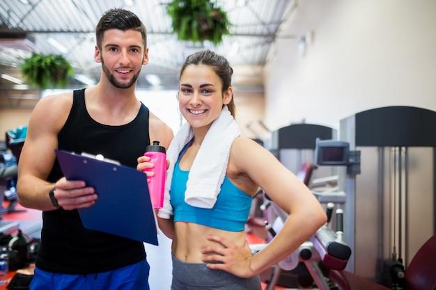 Formateur expliquant le régime d'entraînement à une femme