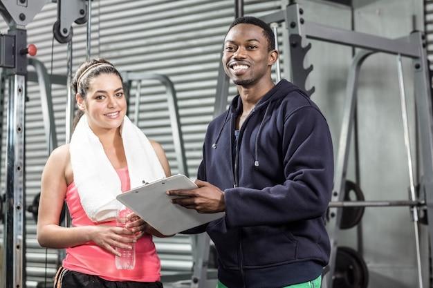 Formateur et femme regardant un plan d'entraînement au gymnase