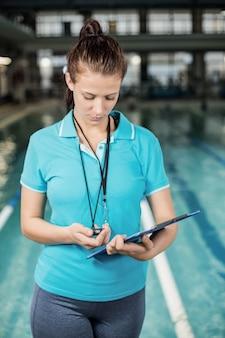 Formateur femme tenant un presse-papiers à la piscine