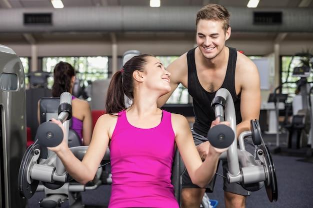 Formateur homme aidant une femme sportive au gymnase