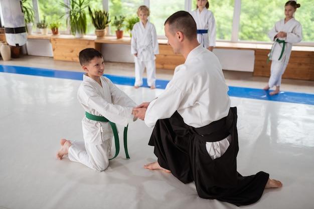 Formateur se serrant la main. entraîneur d'aïkido serrant la main de son petit élève tout en le soutenant avant de pratiquer