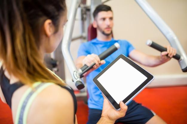Formateur travaillant avec l'athlète à la machine de poids