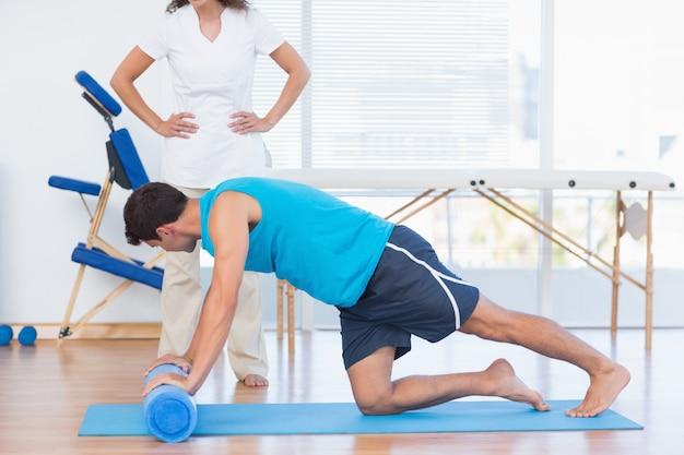 Formateur travaillant avec l'homme sur un tapis d'exercice