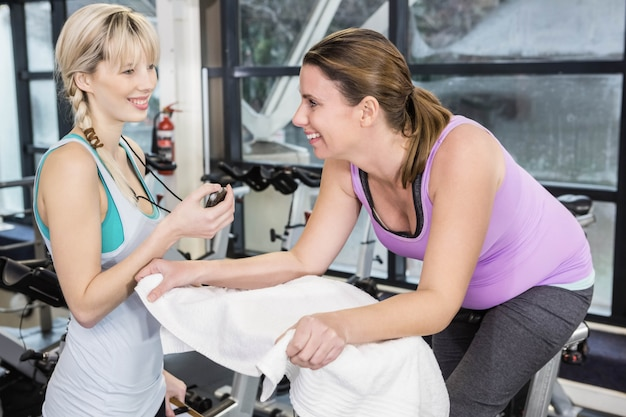 Formateur utilisant un chronomètre pendant qu'une femme enceinte utilise un vélo d'exercice au gymnase