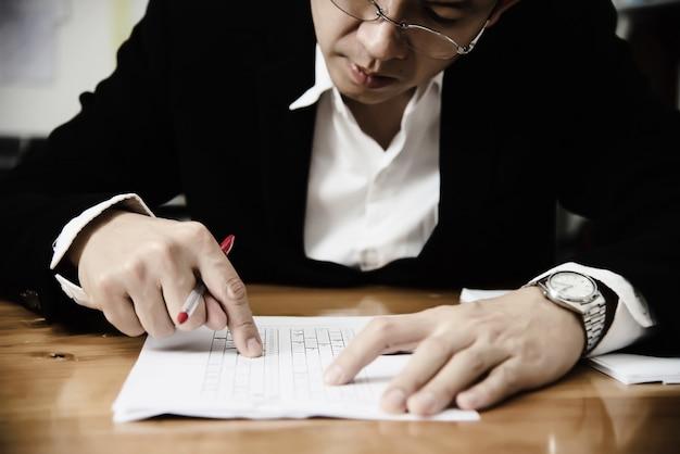 Formateur vérifiant l'examen à choix multiples de feuille de réponses - éducation des personnes travaillant avec le concept de test