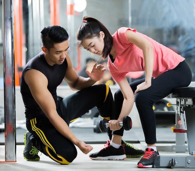 Les formateurs apprennent à une femme asiatique à soulever un haltère. dans la façon dont ils exercent dans la salle de gym.