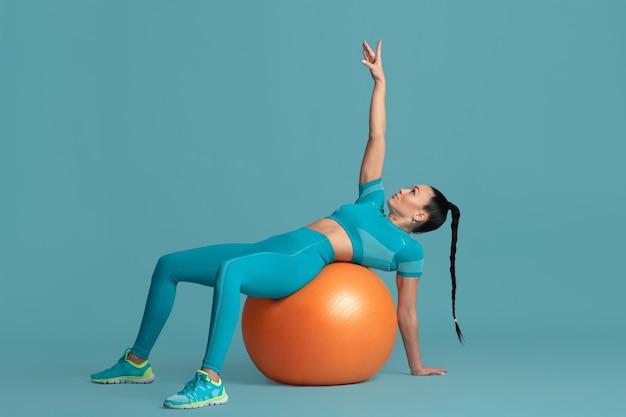 Formation abs. belle jeune athlète féminine pratiquant en studio, portrait bleu monochrome