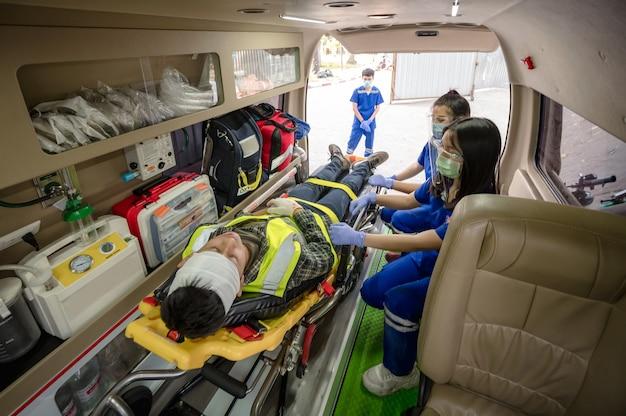 Formation aux premiers secours pour transférer le patient, perte de sensation ou perte de mouvement normal. l'équipe paramédicale transfère un homme sur une civière d'ambulance dans une voiture d'urgence.