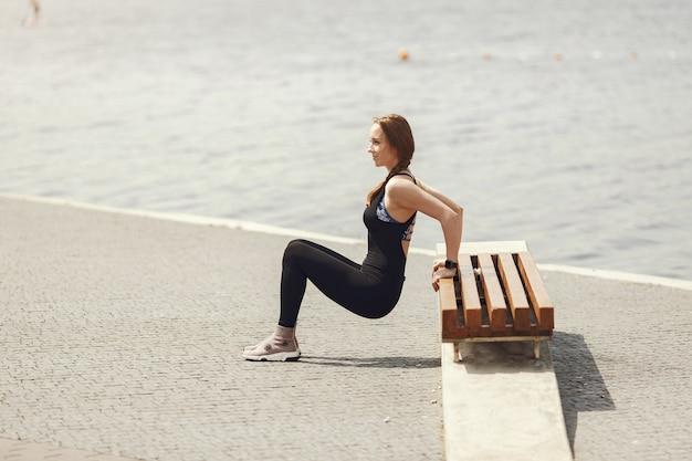 Formation de belle fille. fille de sport dans un vêtement de sport. femme au bord de l'eau.