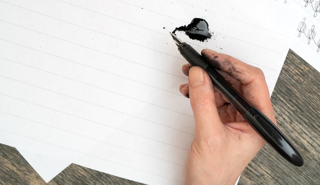 Formation à la calligraphie. stylo-plume dans les mains tachées d'encre.