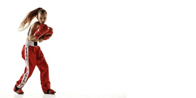 Formation de combattant de kickboxing jeune femme isolée sur fond blanc. fille blonde caucasienne en vêtements de sport rouges pratiquant les arts martiaux. concept de sport, mode de vie sain, mouvement, action. 2020.