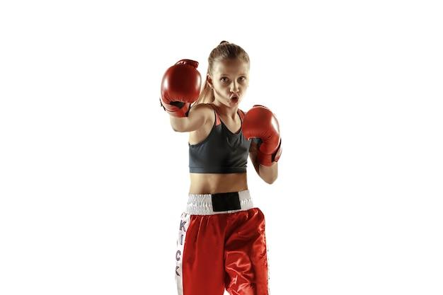 Formation de combattant de kickboxing jeune femme isolée sur mur blanc. fille blonde caucasienne en tenue de sport rouge pratiquant les arts martiaux. concept de sport, mode de vie sain, mouvement, action, jeunesse.