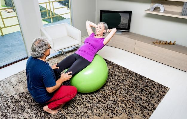 Formation de couple de personnes âgées actives avec ballon suisse à la maison