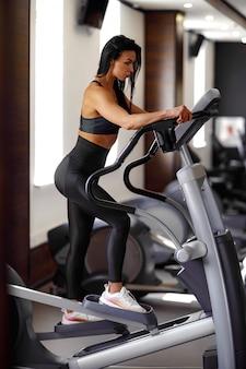 Formation dans le gymnase fitness girl coach travaillant sur la machine step et montrant sa silhouette posant dans un costume de sport