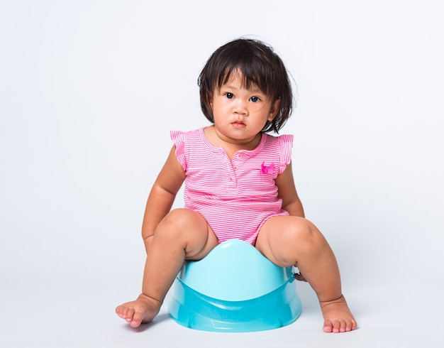 Formation d'éducation de bébé fille à s'asseoir sur un pot de chambre bleu ou un pot