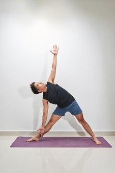 Formation d'entraînement de planche d'homme de forme physique au fond blanc à l'intérieur. le jeune homme fait de l'exercice. mode de vie sain, concept de gymnastique