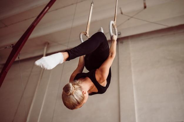 Formation de femme à faible angle sur les anneaux de gymnastique