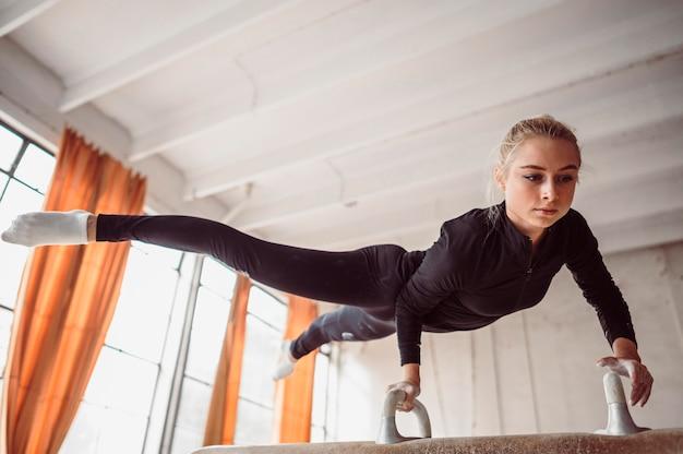 Formation de jeune femme à faible angle pour le championnat de gymnastique