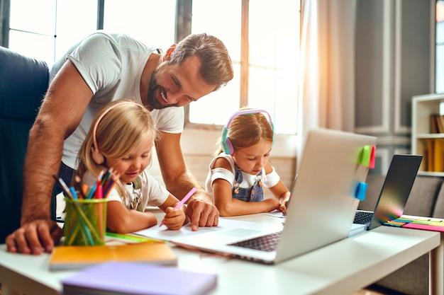 La formation en ligne. deux sœurs écolières au casque écoutent des cours sur des ordinateurs portables. papa aide ses filles à étudier. l'école à la maison en période de pandémie et de quarantaine.