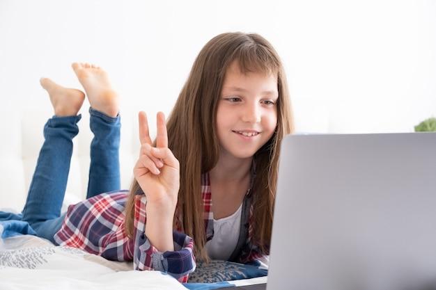 Formation en ligne à distance. écolière étudiant avec ordinateur portable numérique et faire ses devoirs d'école allongé sur le lit à la maison