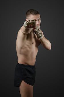 Formation de muay thai combattant musculaire sur la surface sombre avec des cordes de chanvre sur les mains