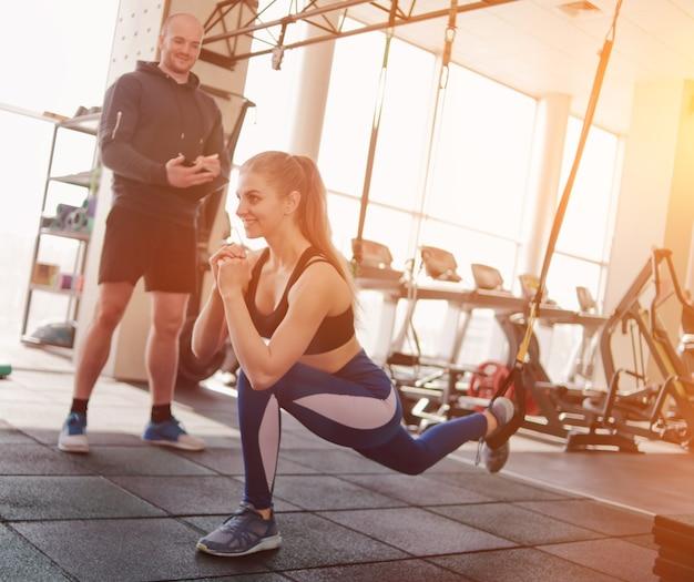 Formation sous la supervision d'un entraîneur personnel. entraînement fonctionnel. femme faisant de l'exercice avec des sangles de futness dans la salle de sport