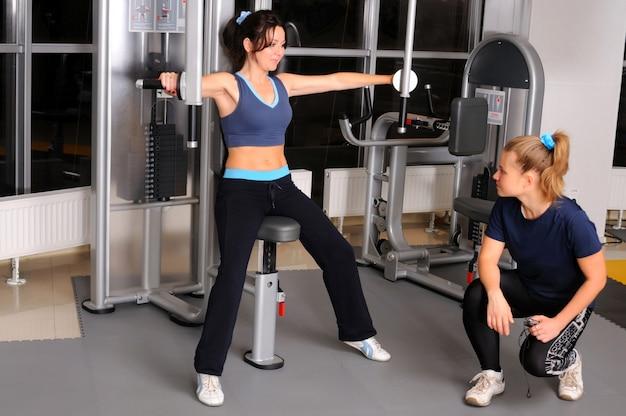 Formation sportive fille brune assise sur une machine de fitness et exercer les muscles des bras sous la supervision d'un formateur