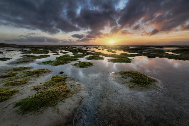 Formations de terres vertes dans l'océan sous le ciel coucher de soleil nuageux