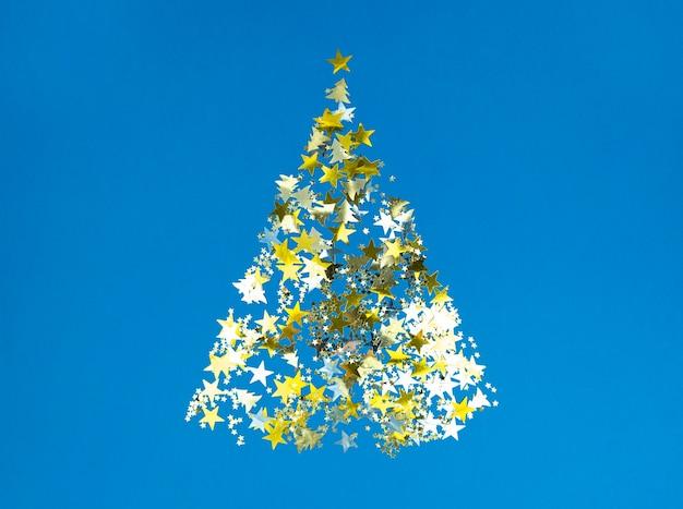 Forme d'arbre de noël d'étoiles de confettis dorés sur fond de papier bleu.