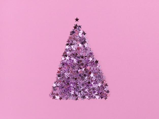 Forme d'arbre de noël d'étoiles de confettis sur papier rose. mise à plat monochrome festive.