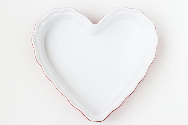 La forme en céramique en forme de coeur est située sur un fond blanc, vue du dessus