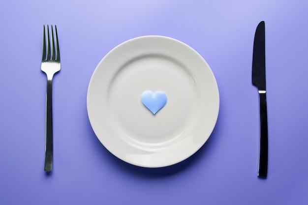 Forme de coeur sur assiette avec fourchette et couteau