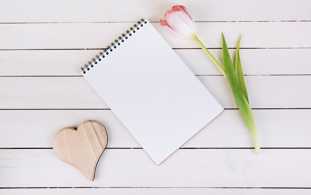Forme de coeur en bois; bloc-notes spirale vierge et tulipe sur table en bois