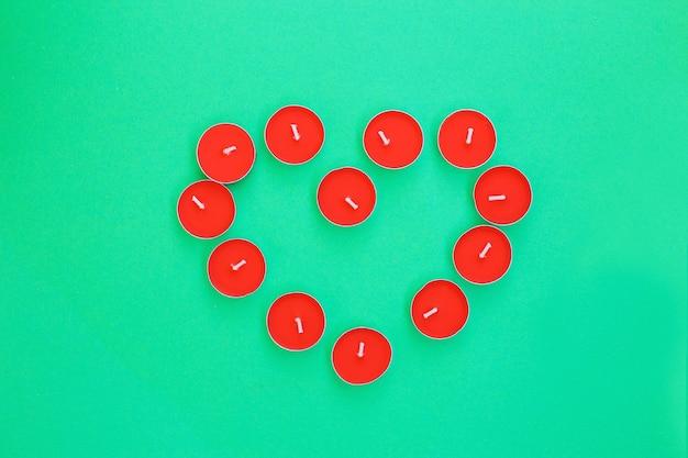 Forme de coeur de bougies chauffe-plat rouges sur fond vert vue de dessus concept d'amour et de romance