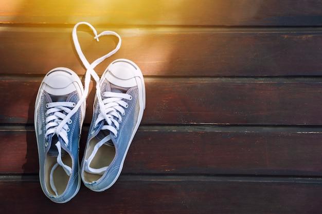 En forme de cœur avec des chaussures ficelle sur le plancher en bois avec la lumière du soleil. concept de l'amour