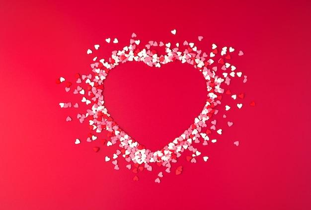 Forme de coeur de confettis sur rouge. vue de dessus