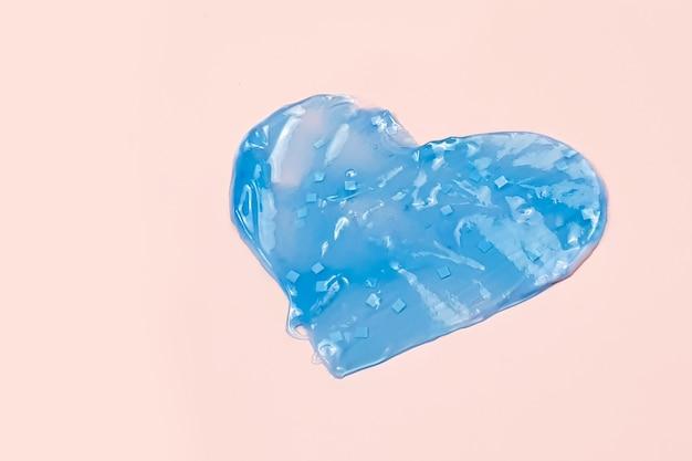 Forme de coeur de crème bleue, de gel ou de dentifrice dans un tableau rose.
