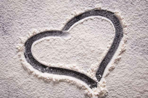 Une forme de coeur dessinée sur de la farine sur un fond noir. fermer.