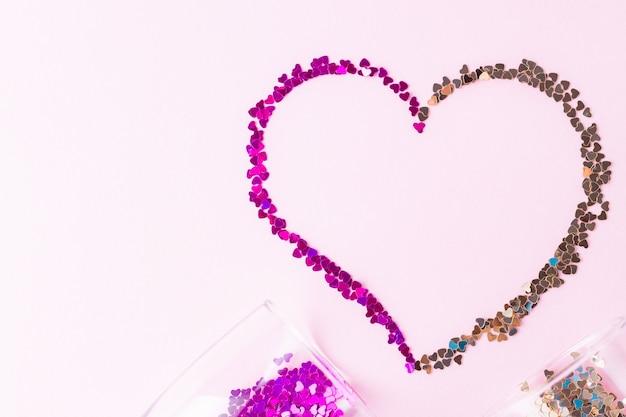Forme de coeur. deux verres de champagne avec des éclaboussures de confettis en forme de coeur sur fond rose