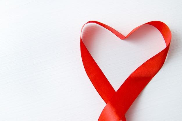 En forme de coeur fait de ruban rouge sur fond en bois blanc