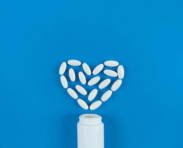 Forme de coeur faite de comprimés blancs et bouteille médicale sur fond bleu.