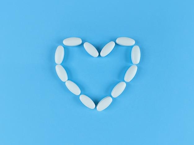 Forme de coeur faite de comprimés blancs sur fond bleu, plat