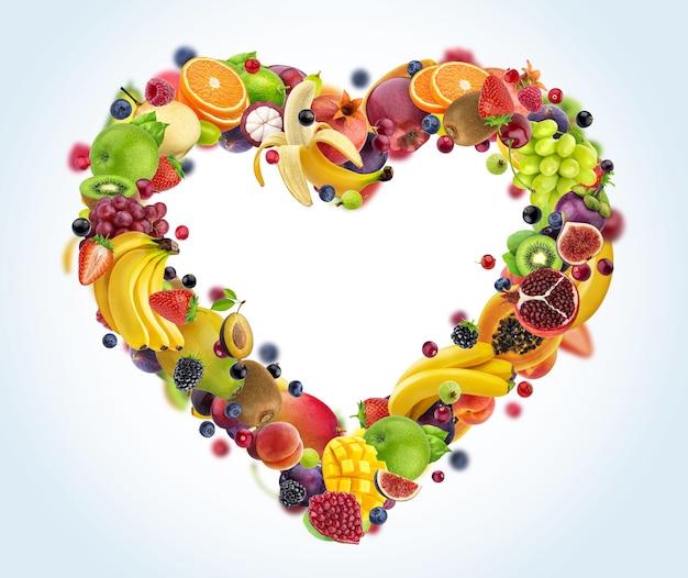 Forme de coeur faite de différents fruits et baies, symbole de coeur isolé sur fond blanc avec un tracé de détourage, concept d'alimentation saine
