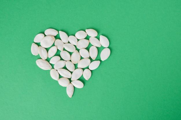 Forme de coeur faite de graines de citrouille sur fond vert. vue de dessus de l'espace de copie